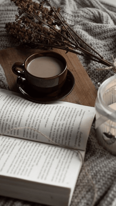 a book on a desk next to a coffee